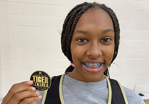 Apryl Vann-Jackson holds up her Tiger S.T.R.I.P.E.S. Medallion.